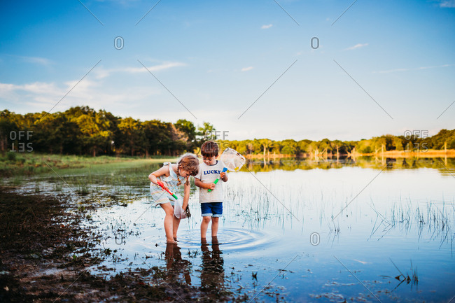 Young girl and boy looking at fish they caught in a net at the lake
