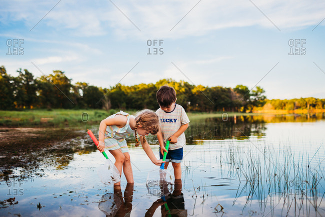 Young girl helping boy catch a fish in his net at the lake