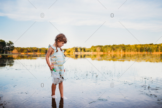 Young girl standing alone looking for fish in water at the lake.