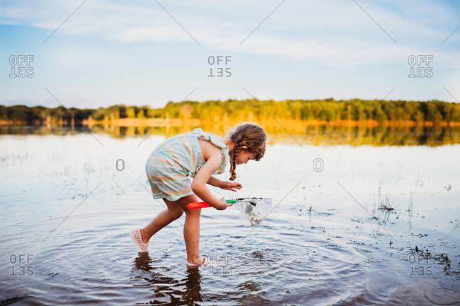 Young girl bending down to see fish in water at the lake