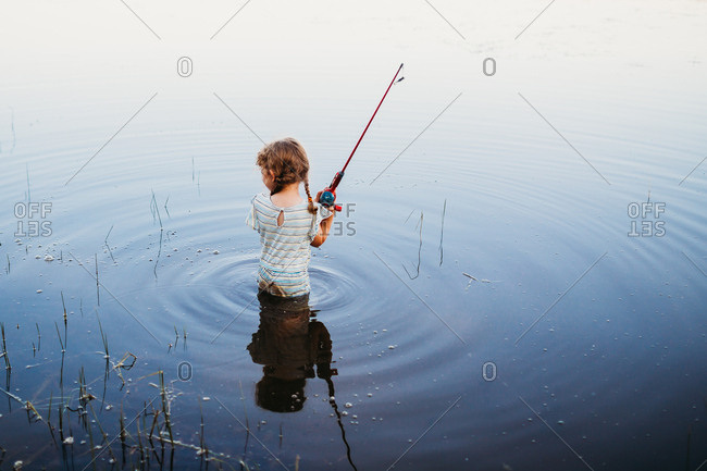 Young girl standing in water at lake holding fishing pole