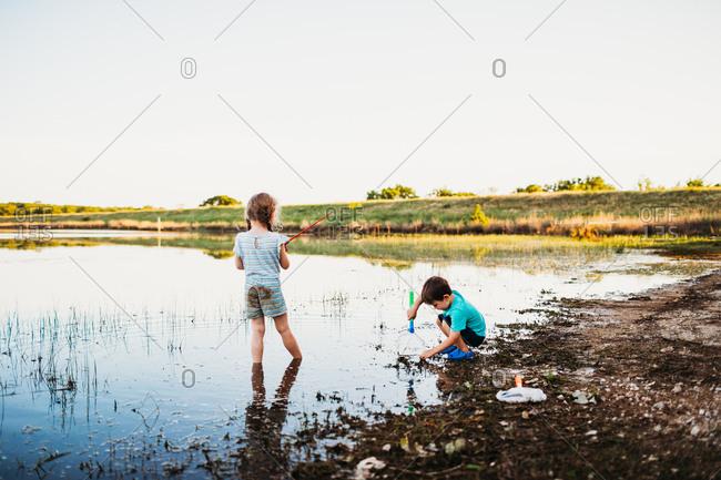 Young girl and boy catching fish with a fishing pole and net at lake