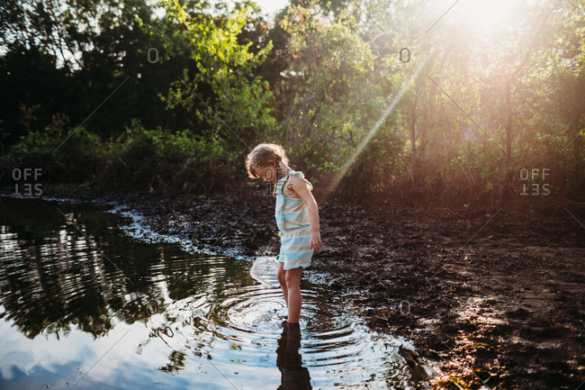 Young girl stepping into water at lake holding a fishing net