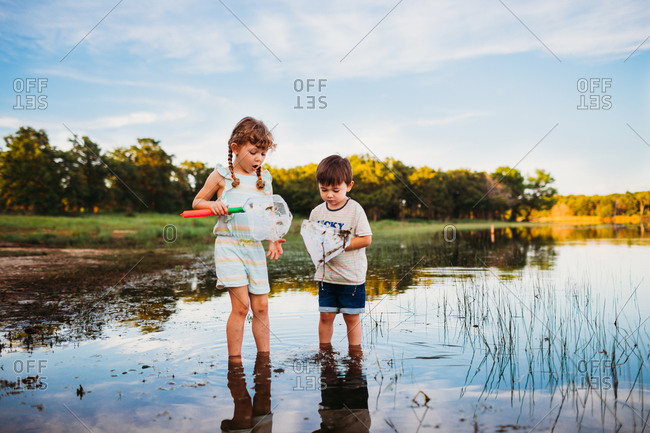 Young girl and boy looking at fish in their fishing nets at the lake