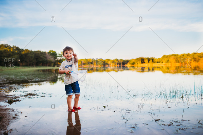 Excited young boy holding small fish he caught at the lake
