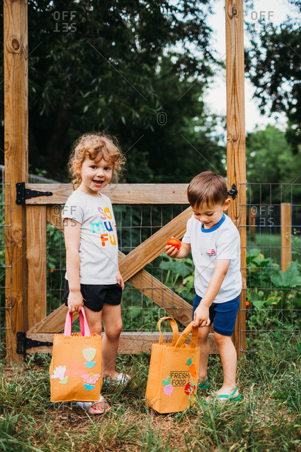 Young boy and girl standing outside backyard garden with vegetables