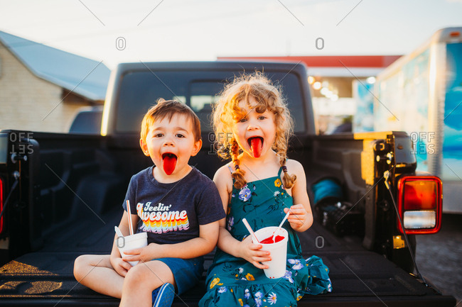 Young boy and girl sticking out red tongue while eating snow cones