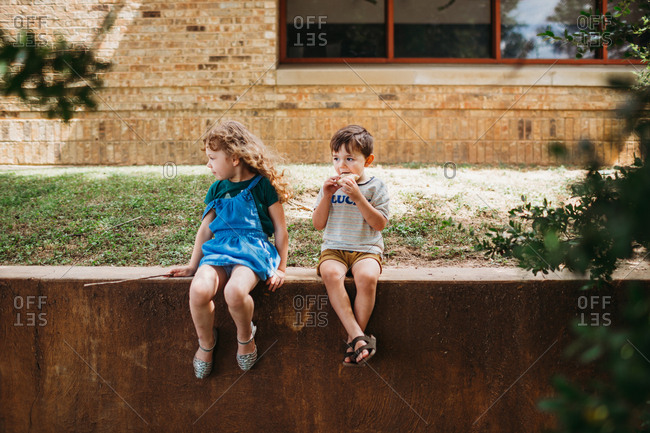 Young girl and boy sitting on wall eating together outside