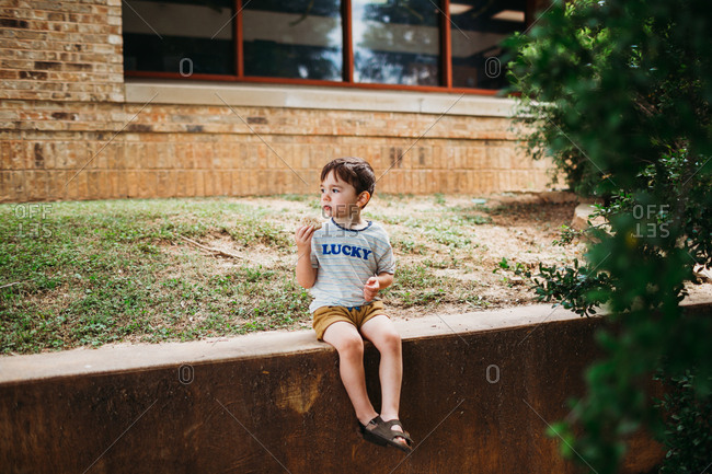 Young boy sitting down eating a snack outside