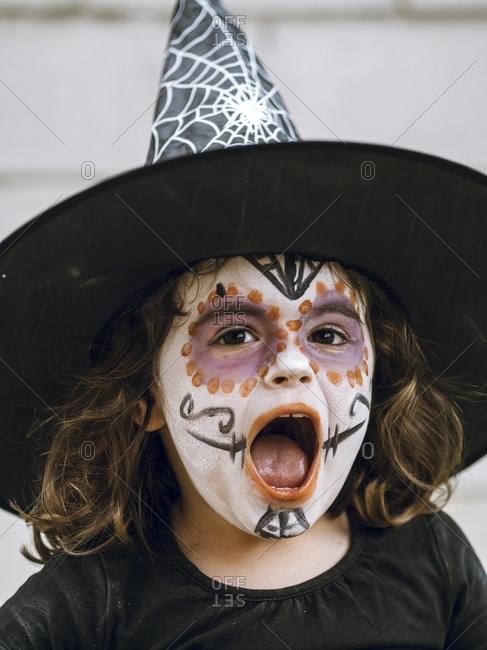 Girl screaming with face painted and disguised for halloween
