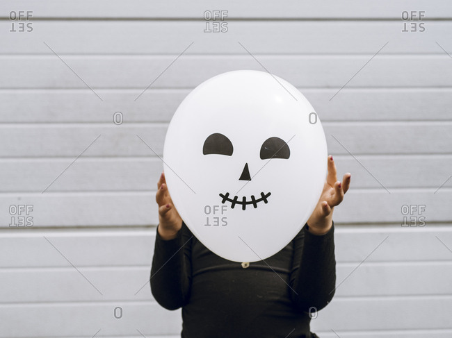 Little girl holds halloween balloon