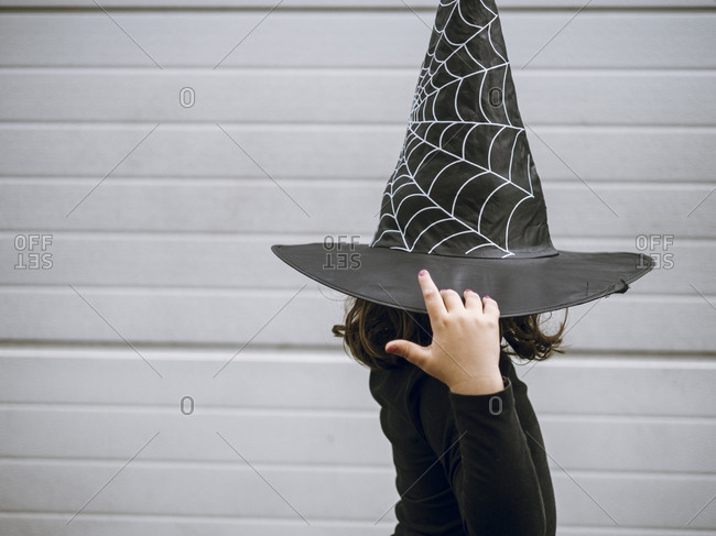 Girl in profile holding witch's cap