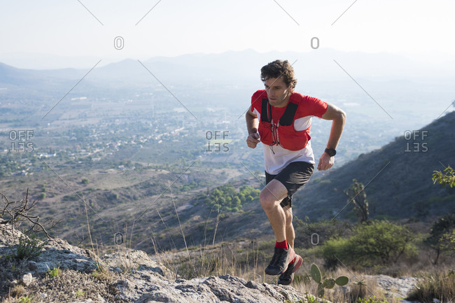 Male trail runner navigating rocky terrain as he climbs the arid mountains near el arenal, hidalgo, mexico.