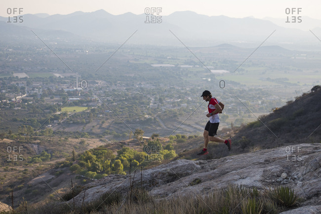 Athletic male trail runner flying down rocky terrain in the arid mountains of el arenal, hidalgo, mexico