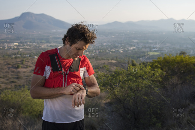 Athletic, male trail runner looks at his watch while the sun sets after going for a run around the trails near the mountains of el arenal, hidalgo, mexico.