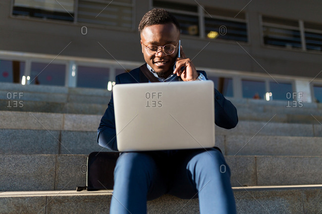 View from below of african american man working with her laptop sitting on a stairs of the street