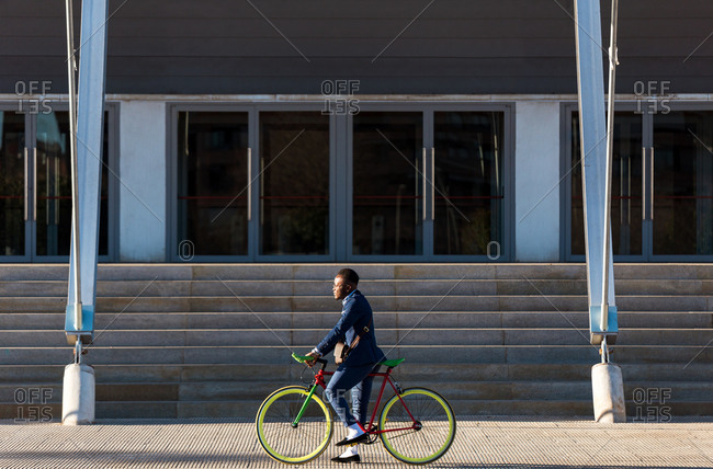 Side view of business man riding with bicycle by the city