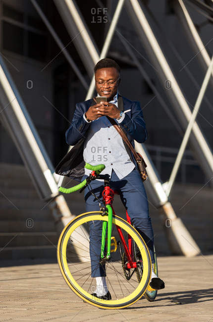 African american business man with bicycle chatting with his mobile phone in a sunny day