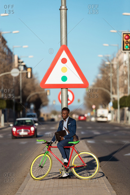 Business man on bike standing in front of a road sign