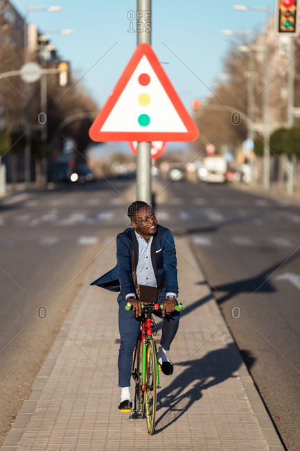 African american man with a suit riding bicycle