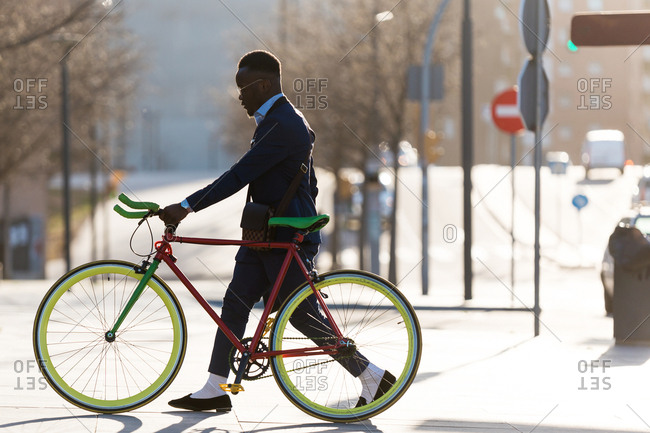 Business man walking by the city holding his bicycle