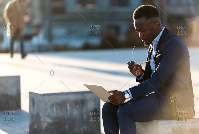 African american business man sitting on a bench of the city working with his laptop