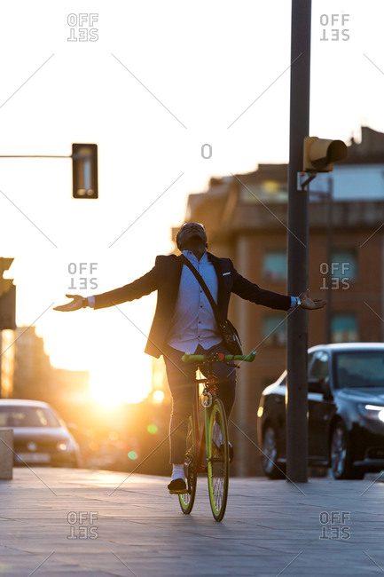 Business man excited and happy cycling by the city without hands in a sunset of summer