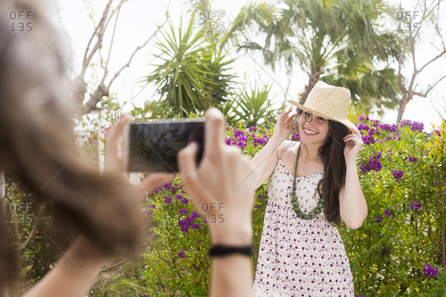 Woman taking photo of smiling friend with smart phone