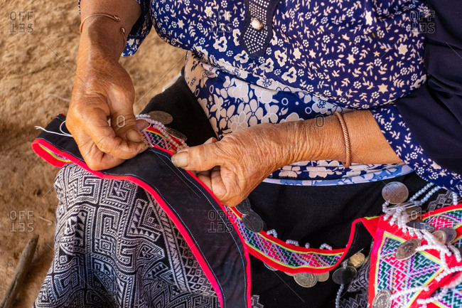 Woman making traditional garments, Vang Vieng, Laos