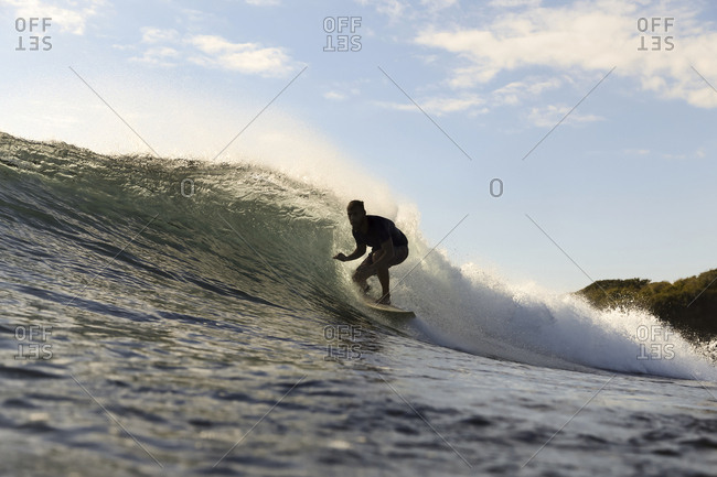 Surfer on a wave at sunset time,Sumbawa island, Indonesia