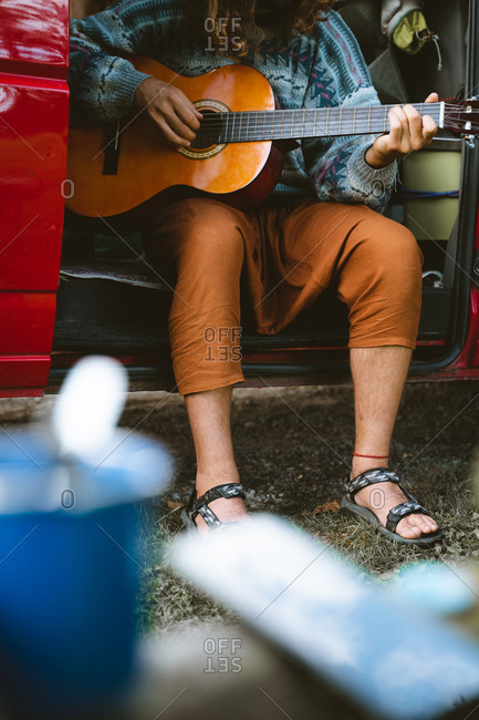 Nomad playing Spanish guitar on the doorstep of his camper van
