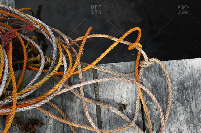 Old worn nautical boat ropes on weathered wooden jetty