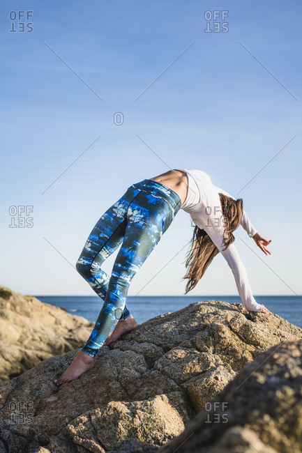 Young woman doing yoga on the rocks at golden hour