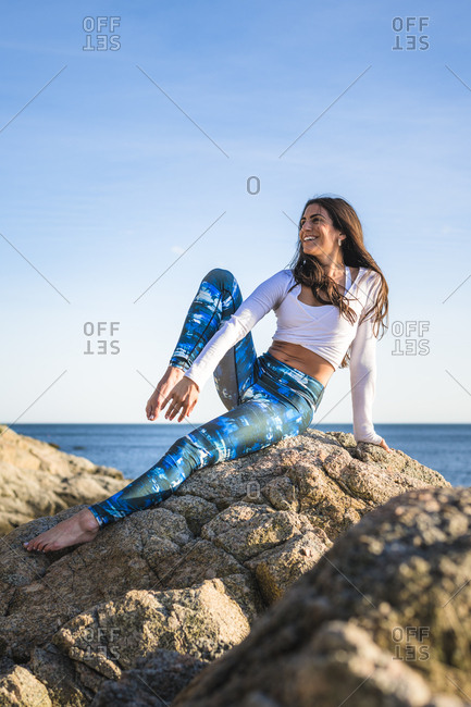 Young woman in a candid moment doing yoga on the rocks at golden hour