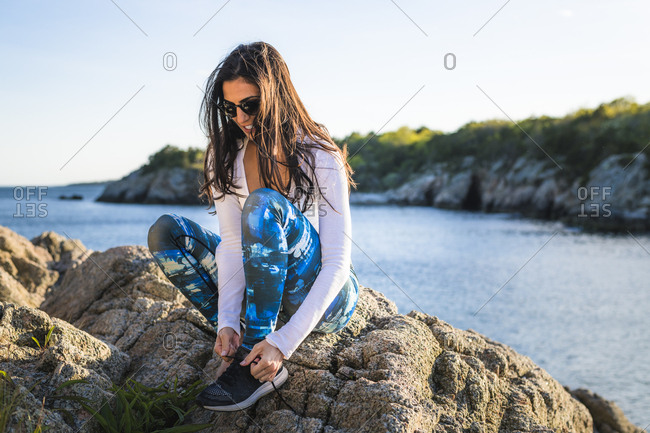 Candid moment of young woman tying her shoes at golden hour