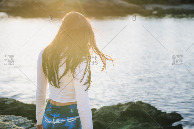 Candid moment of young woman doing yoga on the rocks at golden hour