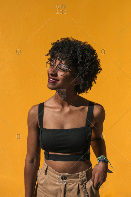 Portrait of young black woman with afro hair on a yellow background