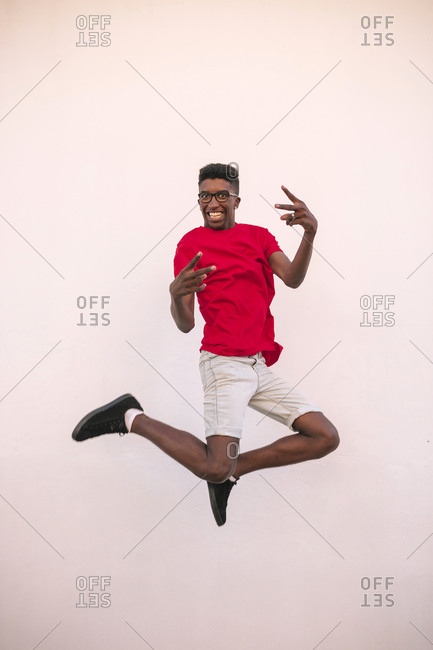 Black teen boy jumping happily on white background