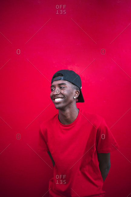 Black teen boy with red shirt smiles on a red background