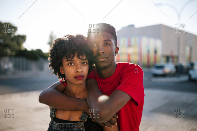 Young black hugs young black woman with afro hair
