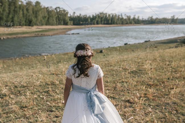 Little girl of communion walking towards a swamp
