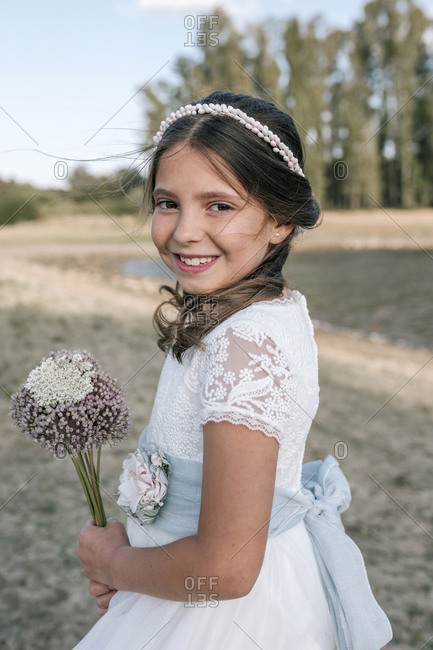 Communion girl with a bouquet of natural flowers in a rustic setting