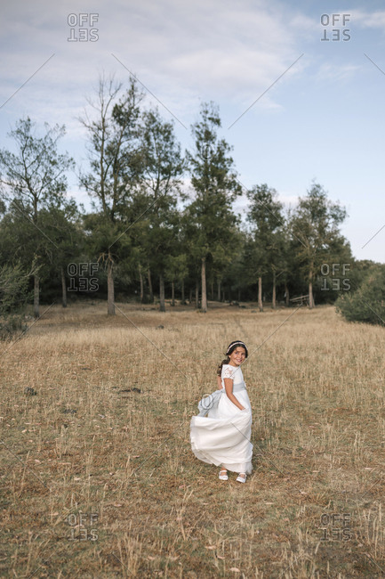 Communion girl dances with her dress in a landscape with trees behind