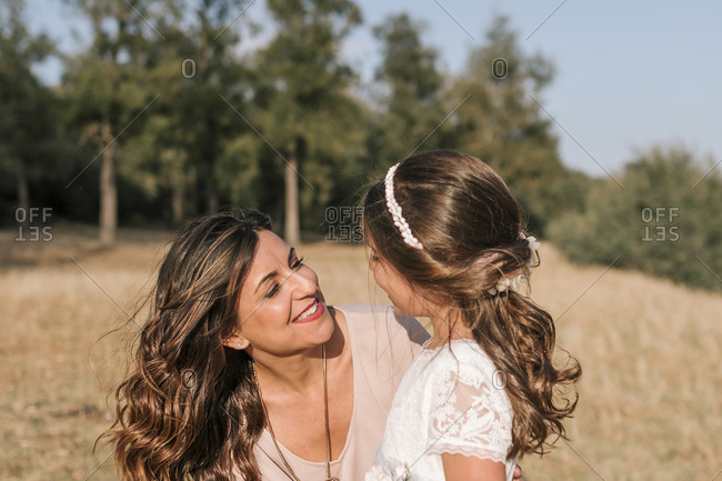 Mother and daughter look at each other in a beautiful rural landscape