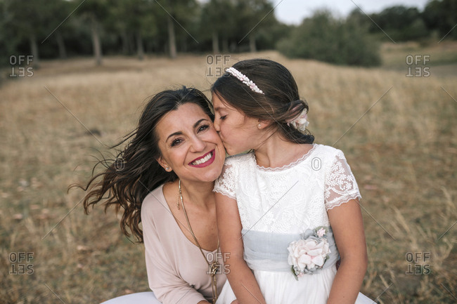 Communion girl kisses her mother in a beautiful rural landscape