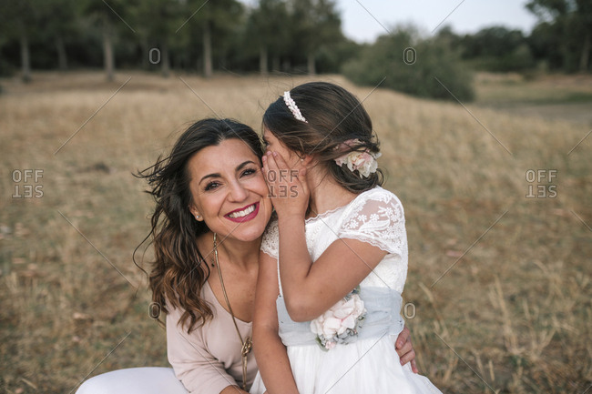 Communion girl tells a secret to her mother's ear