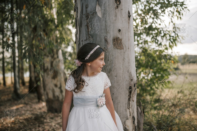 Communion girl is in a forest of tall trees