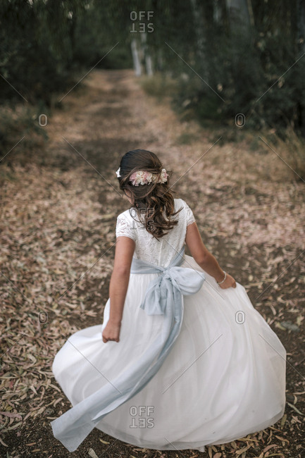Communion girl moves the skirt of her dress in a beautiful forest