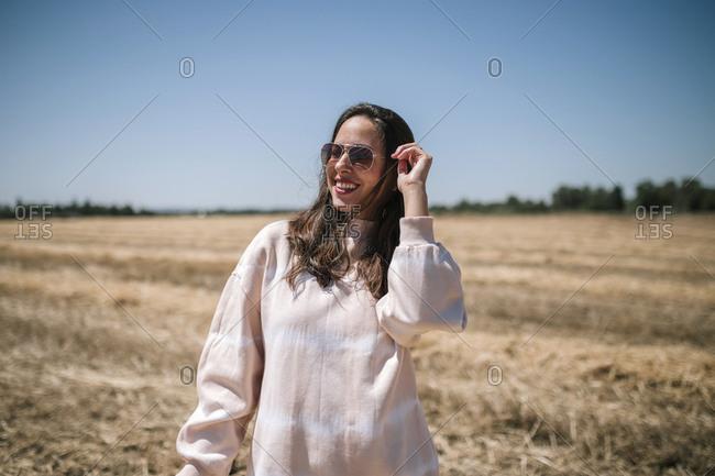 Woman in a straw field receives sunlight