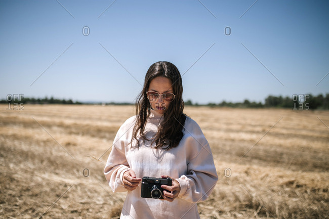 Woman in a straw field making photos with a camera